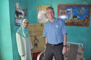 Rotarian Chris Offer (right) and Dr. Noha Farag from the CDC visit a traditional healer's hut as part of a polio surveillance team in Sudan. A Rotary poster about paralysis appears in the background.