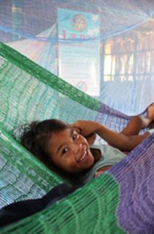 A happy recipient of one of the specially designed mosquito nets.