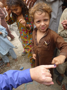A child shows off the purple dye on his pinkie, a sign he has received the polio vaccine.