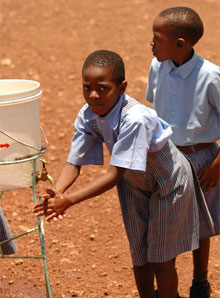Children wash their hands from a spigot in Mwika, Tanzania. Photo courtesy of Walt Schafer