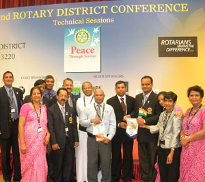 Rotarians from India and Sri Lanka exchange club banners during a Friendship Exchange.
