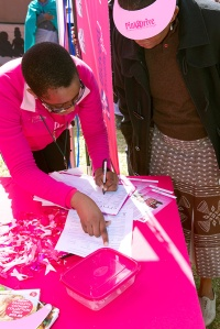 Volunteers provide counseling and share information about breast cancer at a booth in Zandspruit, South Africa. Photo by Anna J Nel