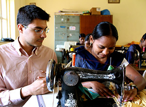 Enrico Ferro visits the vocational training center, where a women learns sewing skills.