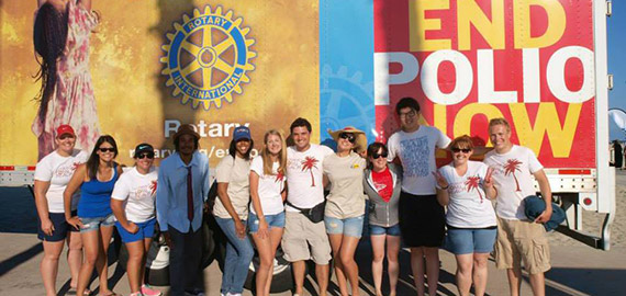 Members of the Rotaract Club of Long Beach pose in front of signs during the sculpture contest.