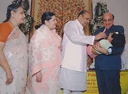 Shri K. Sankarnarayanan, governor of Maharastra, India, administers the polio vaccine to a child being held by former Trustee Ashok Mahajan.