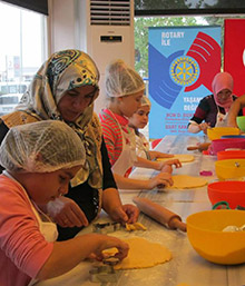 Spouses of Turkish Rotarians help the young chefs with the recipes from the cookbook.