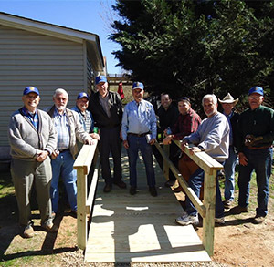 Roy Gandy, left, members of the Rotary Club of Madison, Georgia, and volunteers stand by a ramp they built for a 47-year-old woman who had suffered a severe stroke in January.