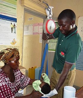 A member of Rotaract weighs a baby before vaccinating the child against polio.