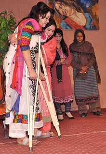 A woman crippled from polio receives help from her mother in a play sponsored by Rotary members in Rawalpindi, Pakistan.