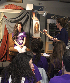 Fine artist Kelly Mellos paints a portrait of one of the visiting students.