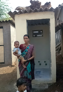 A woman stands in front of her toilet block in Sogav, India.