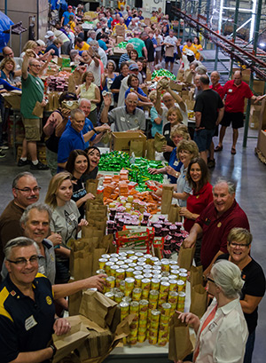 Participants pack sack lunches during the event at Harvesters, a Kansas City area food bank.