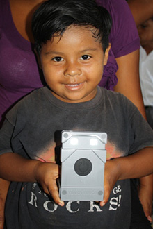 A boy in Belize holds the solar powered light that replaced dangerous Kerosene lamps, provided by Rotary members in Austin, Texas.
