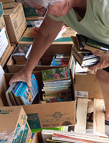 A volunteer sorts and packs books.