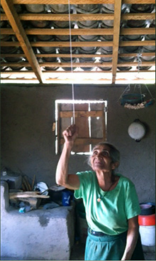 A woman in Chaguiton, Honduras, pulls the string to turn on her new ceiling light. Photo courtesy Neal Beard
