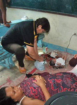 Teodora Lucero attends to the newborn at the evacuation center in Laguna.