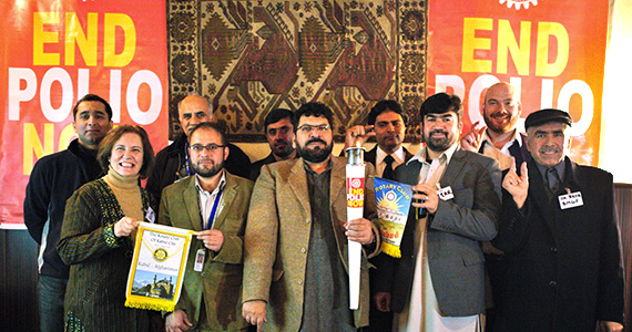Members of the Rotary Club of Kabul hold the Rotary torch during its stop at their club.