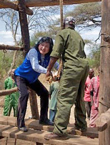 Michiko Mitarai shows Ugandan villagers a Japanese method for drawing water from a well.
