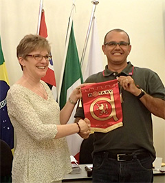 Renée Riley-Adams exchanges club banners with a member of the Rotary Club of Ubatuba, São Paulo, Brazil.