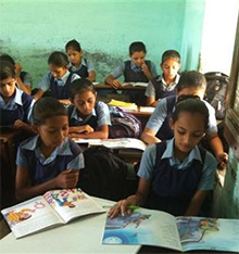 Children read books they received through Gyan Jyot, a program of the Rotary Club of Baroda Sayajinagari.