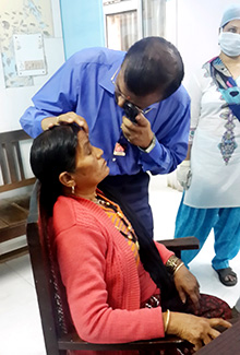 A member of the medical team inspect a patient for cataracts.
