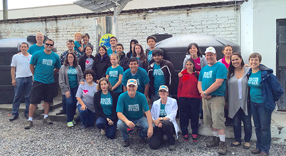 Rotary members, students, and teachers in front of the water purification system in San Miguel.