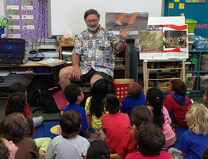 Mike Curtis, a member of the Rotary Club of Poipu Beach, reads to students at Koloa Elementary School. Photo by Rotary Club of Poipu Beach
