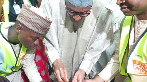 Nigerian President Muhammadu Buhari, center, immunizes a child against polio in his hometown of Daura.