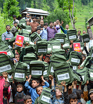 Students in Pakistan's Neelum Valley display the backpacks they received from members of the Rotaract Club of Jhang Saddar.