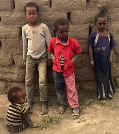 Ethiopian children watch the immunization volunteers.