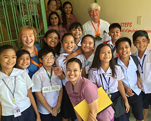 RI Director Julia Phelps, back left, visits a classroom in the Philippines during a trip to rekindle connections with teachers who benefited from a vocational training team.