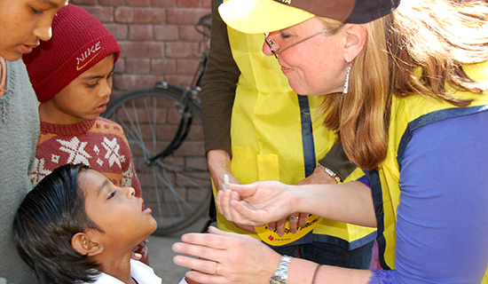 Cynde Covington administers drops of the polio vaccine