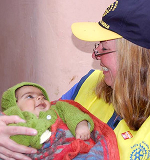 Cynde Covington holds a child awaiting to be immunized against polio.